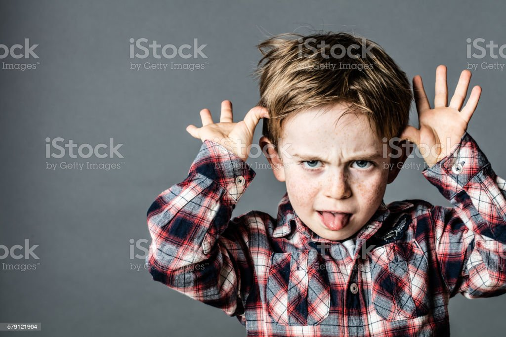 angry little brat enjoying making a grimace for misbehavior stock photo