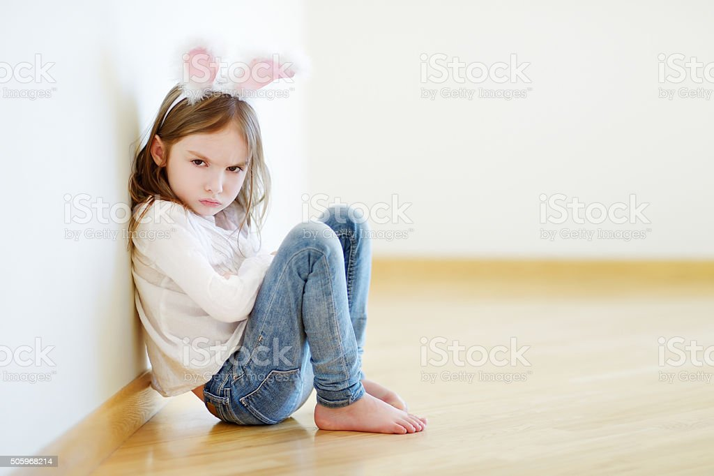 Angry little girl wearing bunny ears stock photo