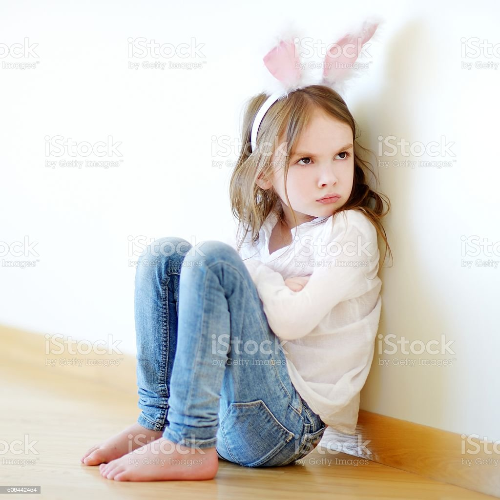 Angry little girl wearing bunny ears stock photo