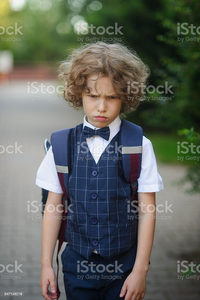 Angry little schoolboy stands in the school yard. stock photo