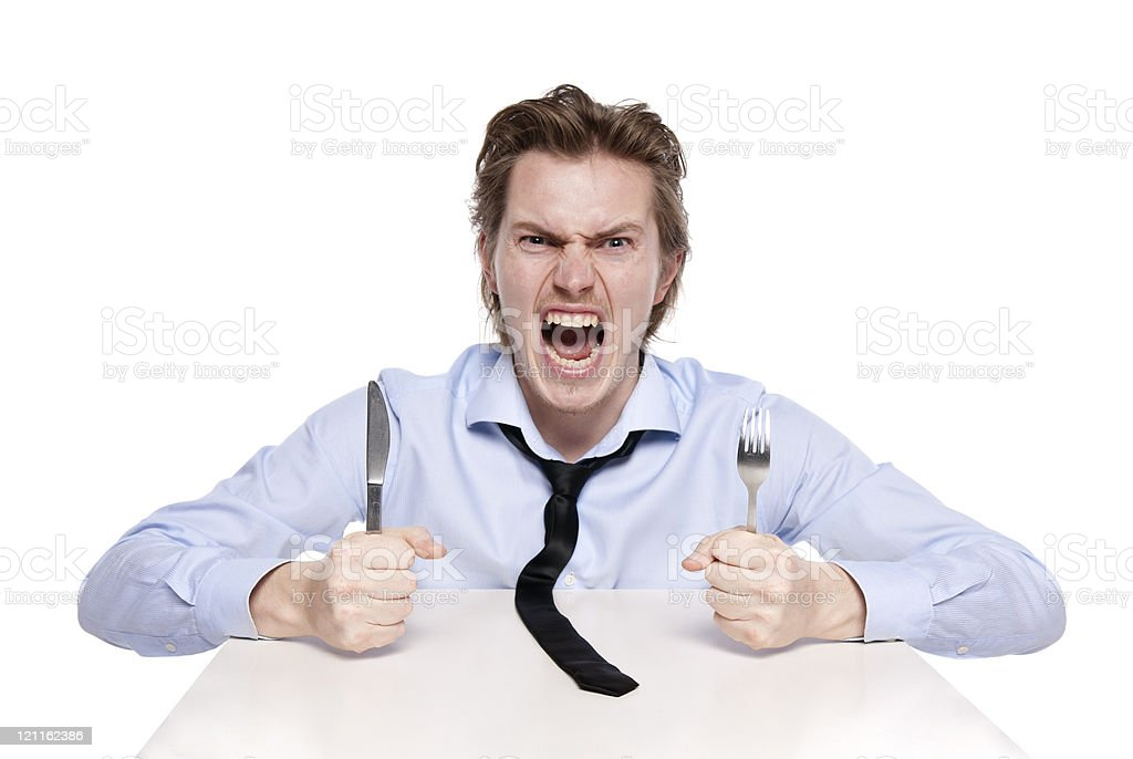 Angry looking young man banging his cutlery on the table stock photo
