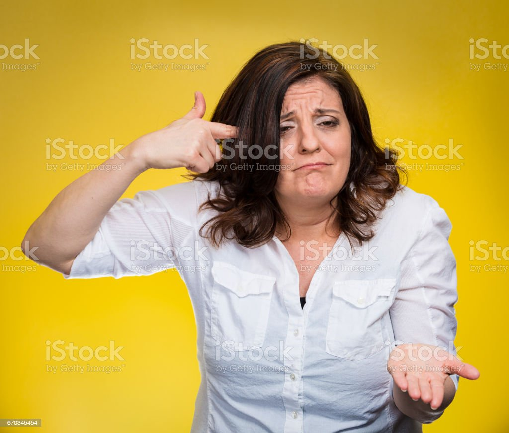 angry mad middle aged woman gesturing with her finger against temple stock photo