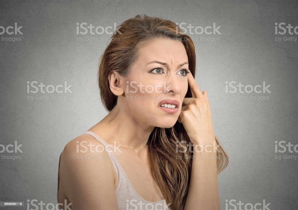 angry mad young woman gesturing with her finger against temple asking are you crazy stock photo