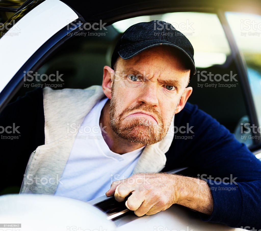 Angry male driver looks through car window, grimacing, fist clenched stock photo