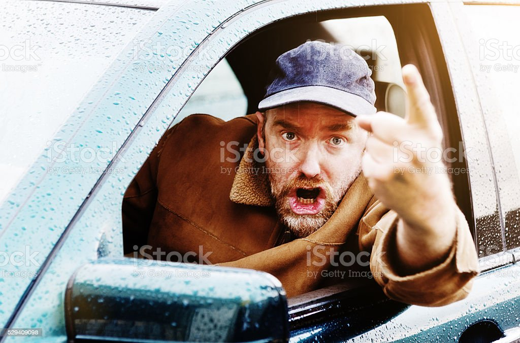 Angry male driver points finger accusingly, shouting  and threatening stock photo