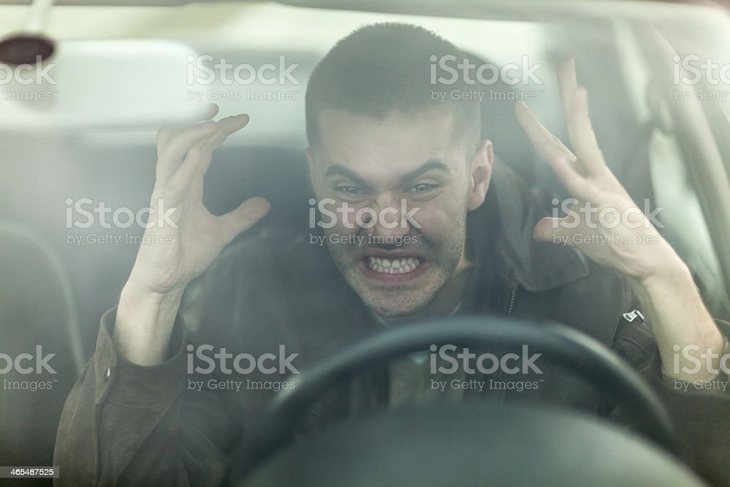 Angry man behind the wheel demonstrating road rage stock photo