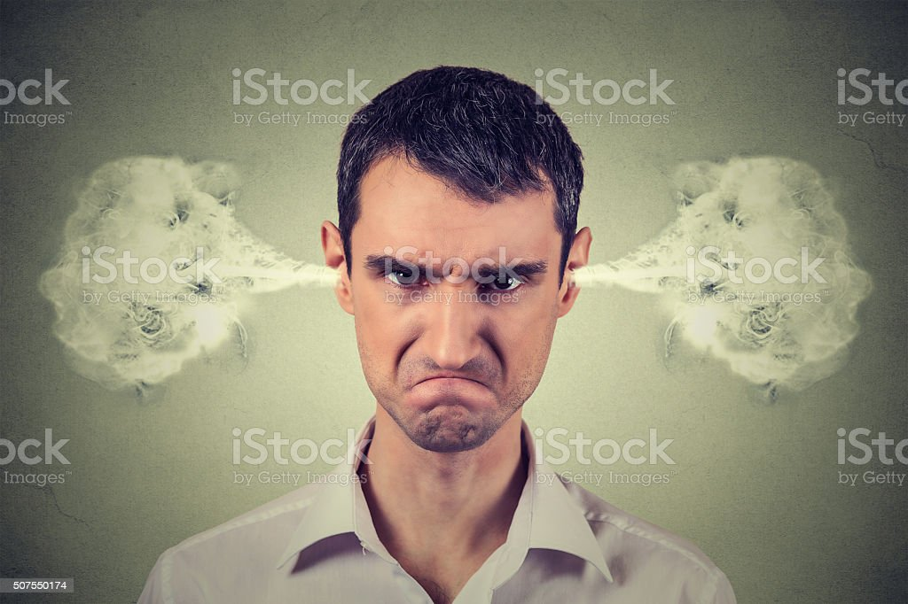 Closeup portrait of angry young man, blowing steam coming out of...