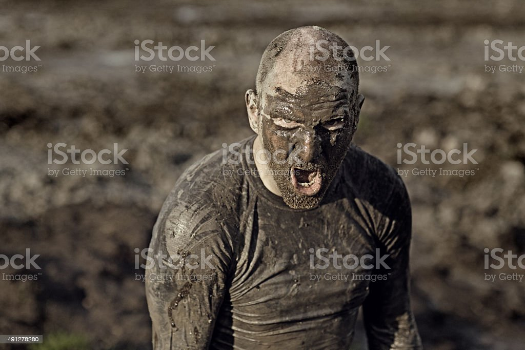 angry man covered in mud shouting stock photo