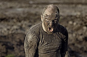 angry man covered in mud shouting