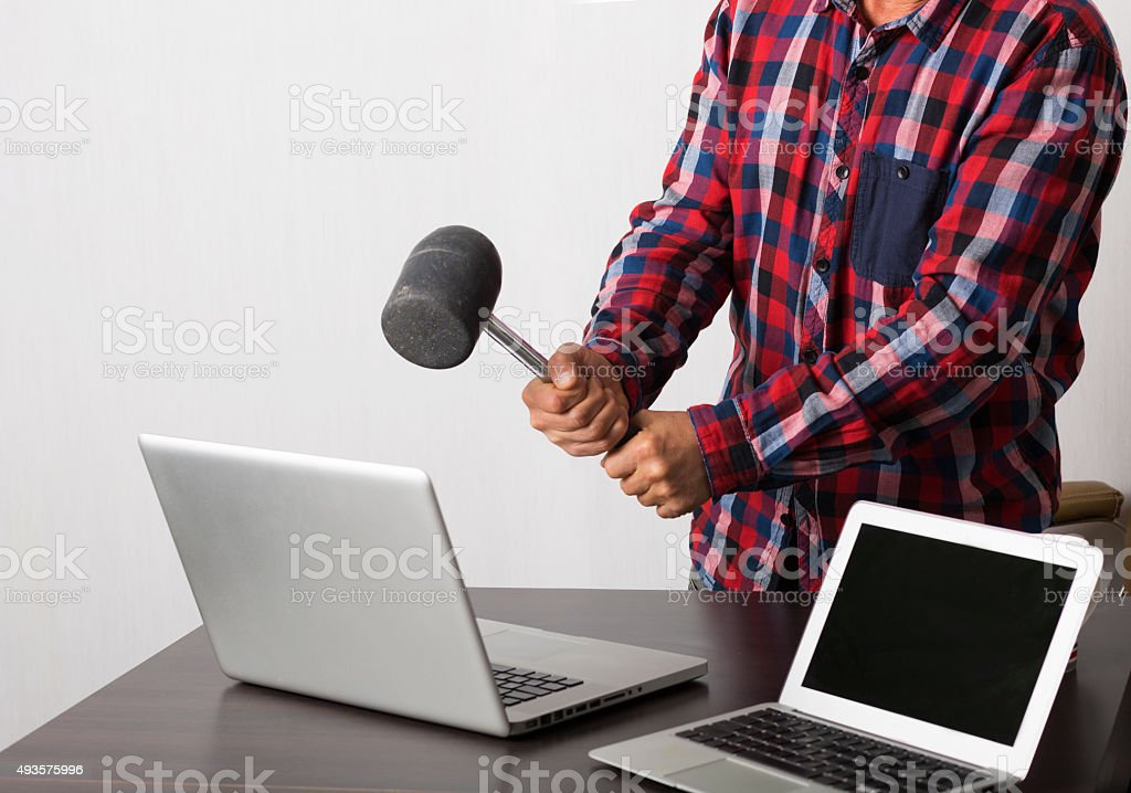 Angry man crashing laptop stock photo