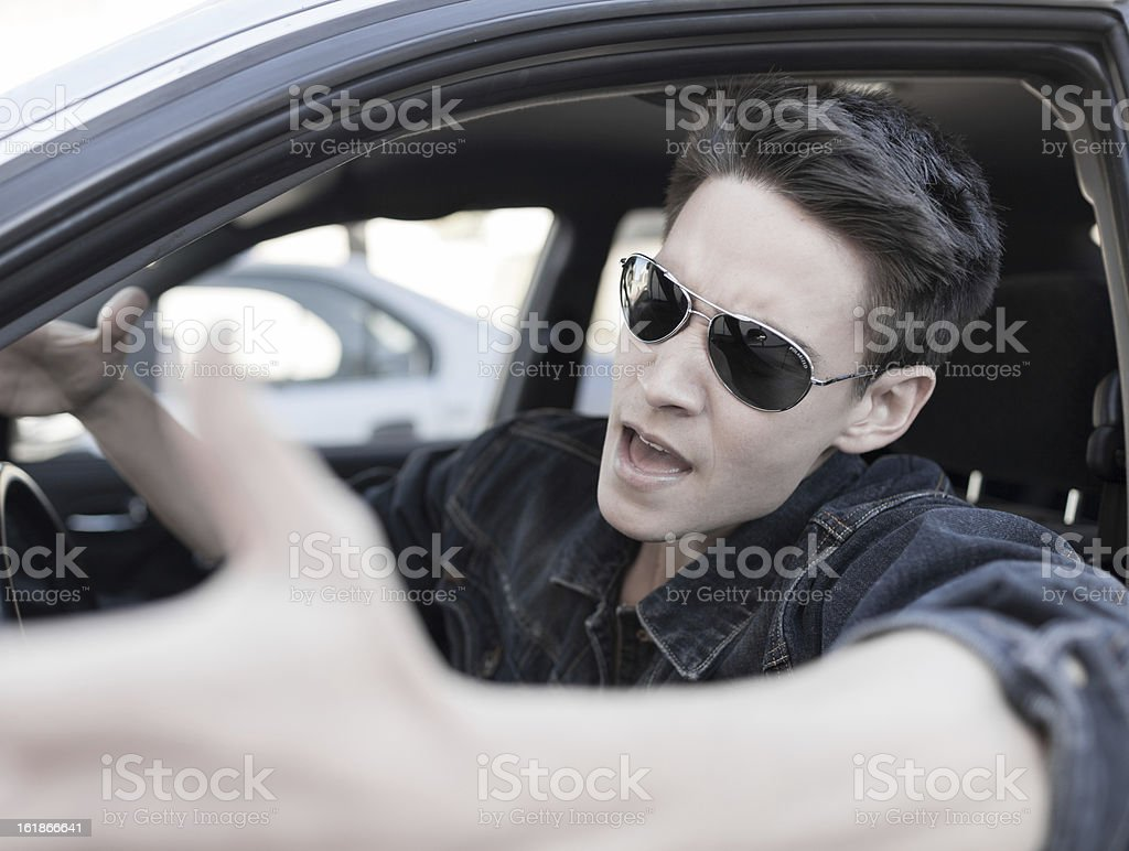 Angry man in car wearing sunglasses making a hand gesture stock photo