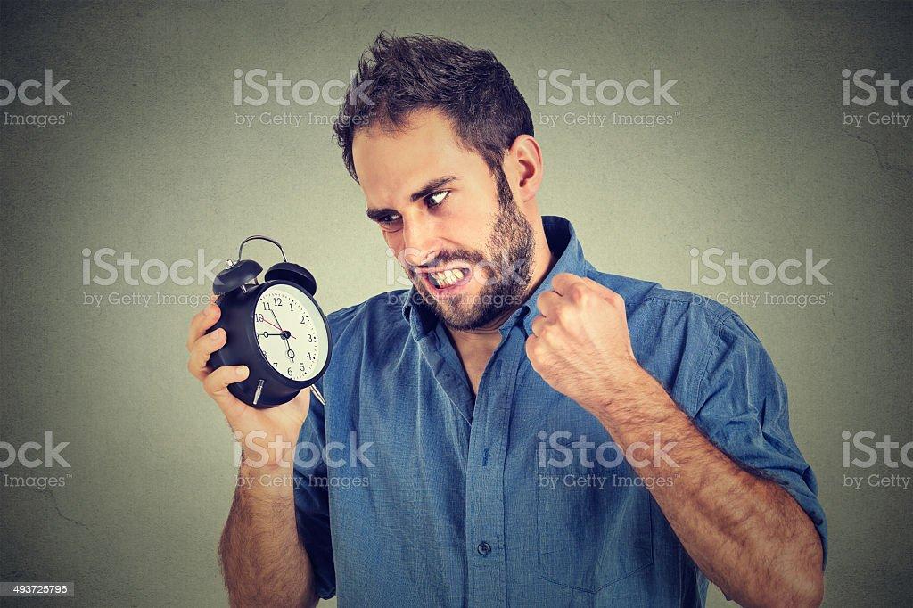 angry man screaming at alarm clock, running late stock photo
