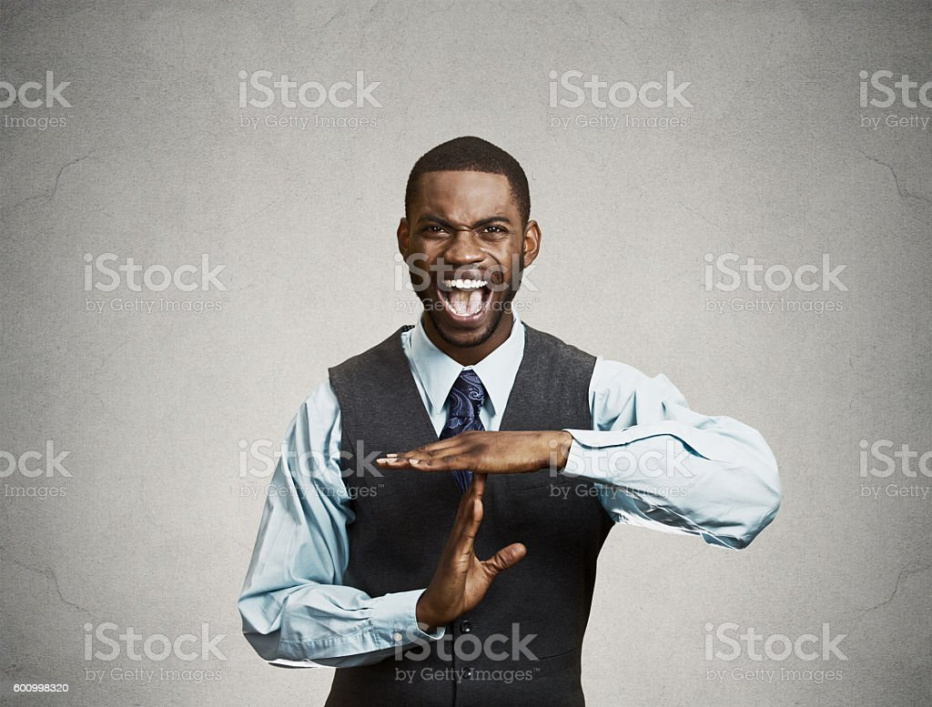 Angry man screaming to stop giving time out gesture stock photo