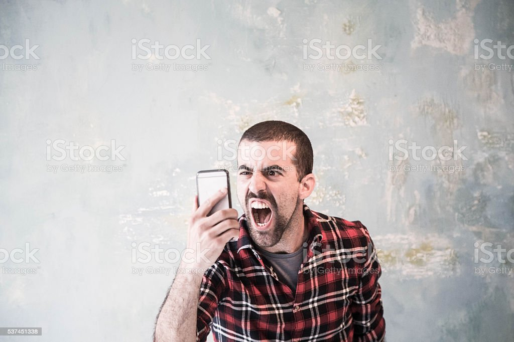Angry man shouting at  cell phone stock photo