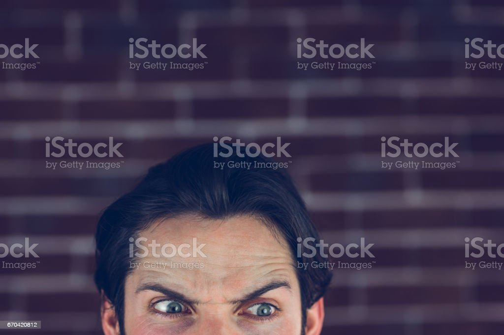 Angry man with raised eyebrows looking away stock photo