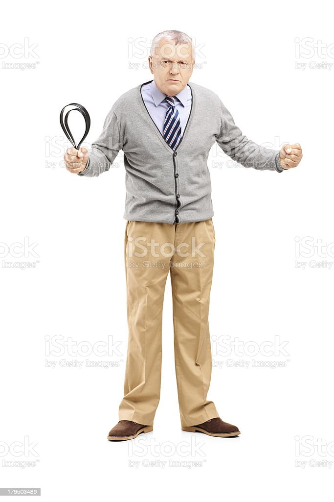 Angry mature man holding a belt and looking at camera royalty-free stock photo