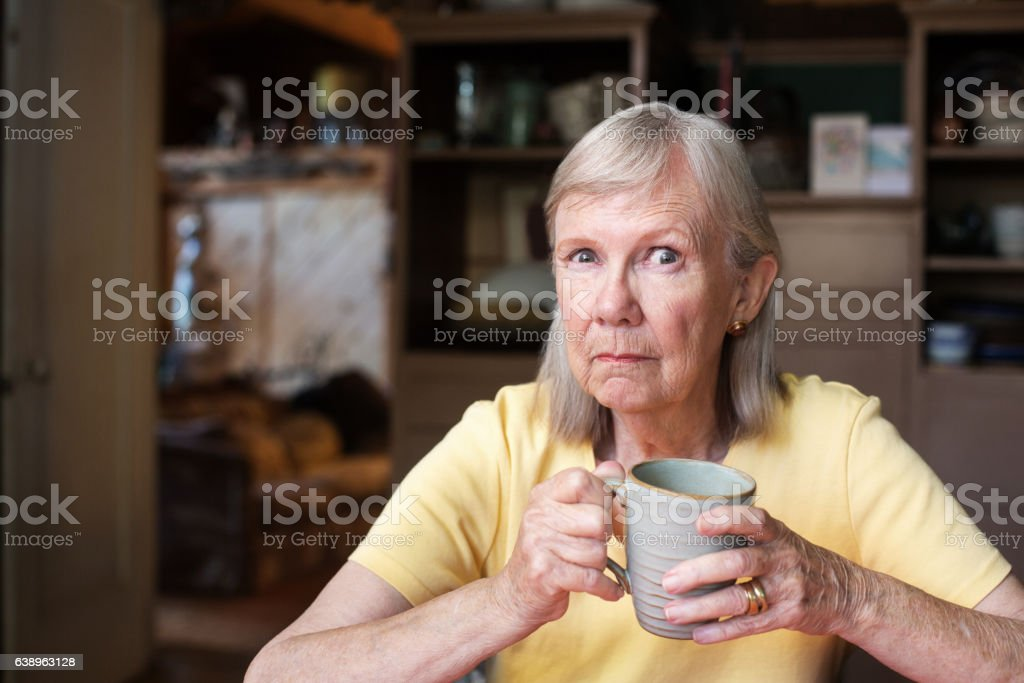 Angry mature woman holding cup stock photo