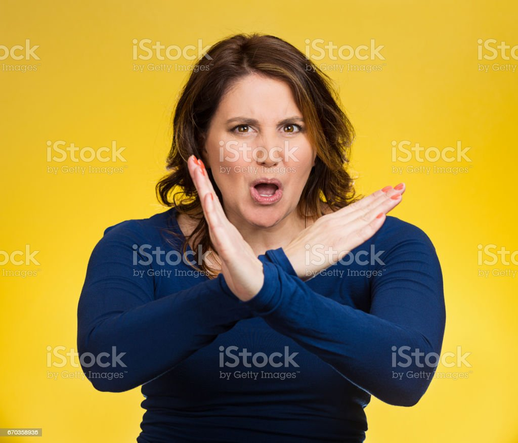 angry middle aged woman with X gesture to stop talking, cut it out, dont go there stock photo