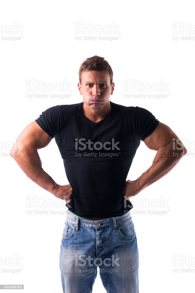Angry muscular young man with fists on his hips stock photo