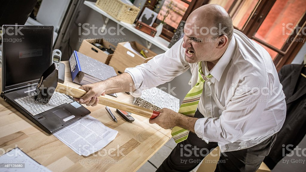 Angry office worker destroying his laptop with a sledgehammer stock photo