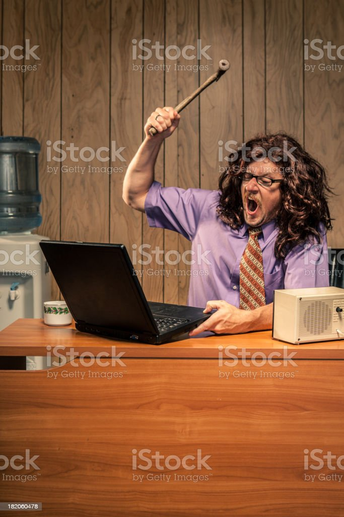 Angry Office Worker With Hammer Smashing Computer Violently stock photo