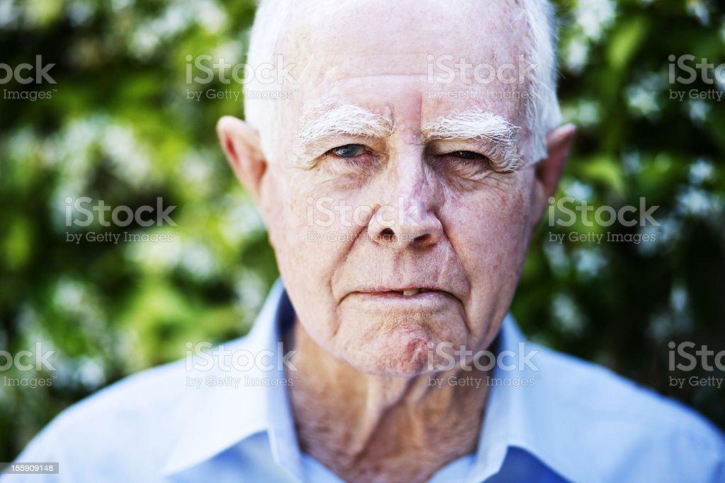 Angry old man glares at camera stock photo