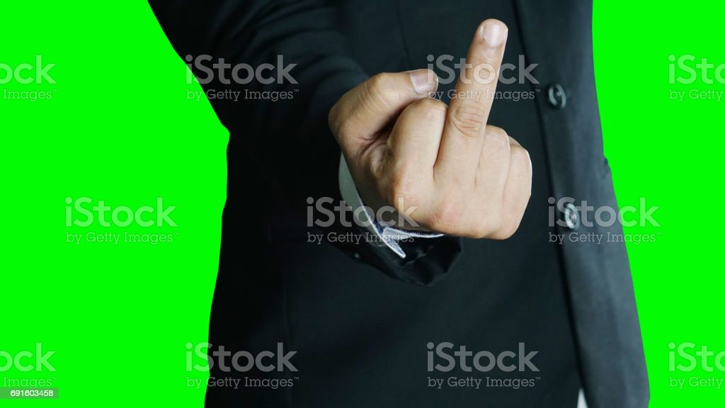 Angry or furious businessman isolated, green screen. A man in black suit show middle finger, fuck you off sign. stock photo