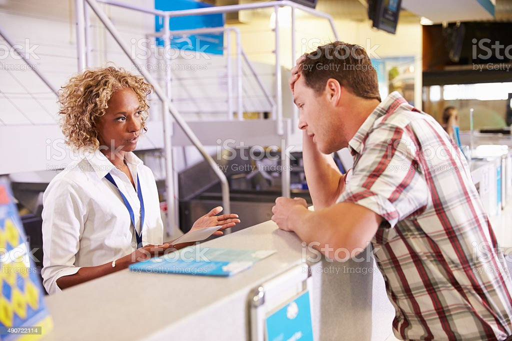 Angry Passenger Complaining To Staff At Airport Check In stock photo