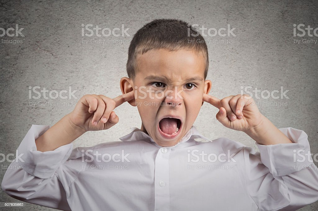 angry pissed off boy plugs his ears with fingers stock photo