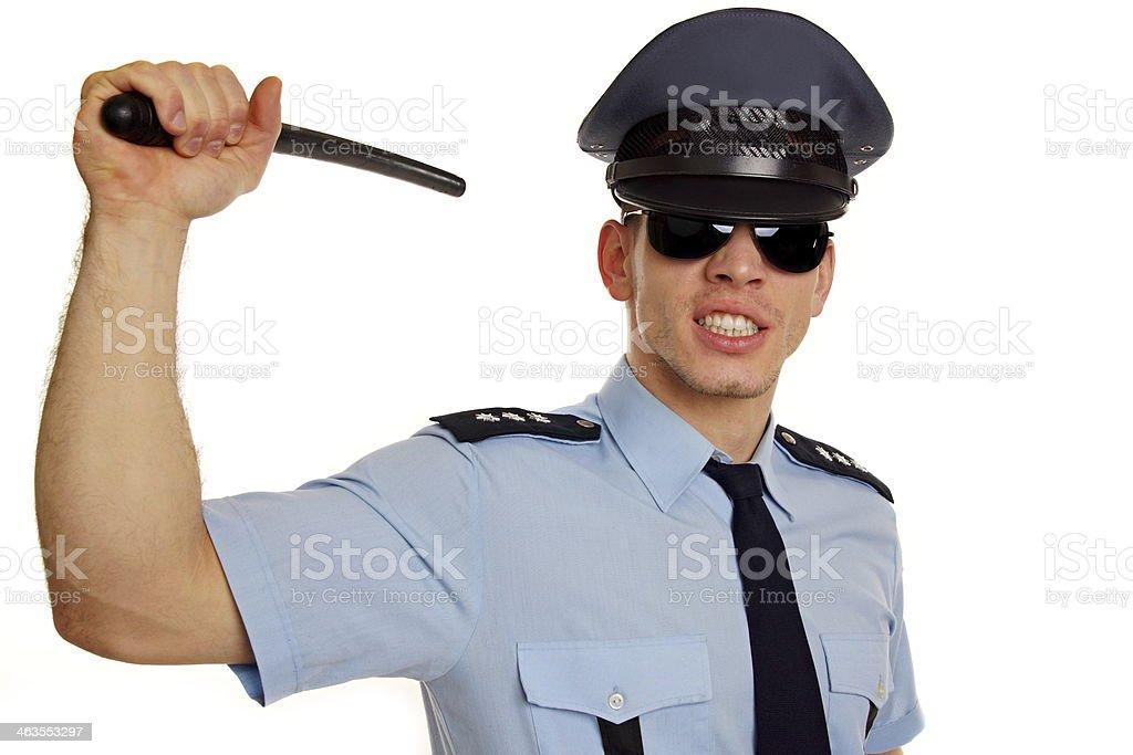 Angry policeman with police baton stock photo