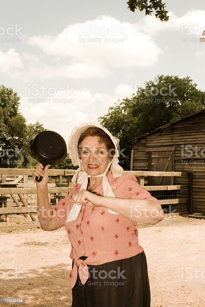 Angry Prairie Woman Threatening with Frying Pan Farmyard Frontier Justice royalty-free stock photo