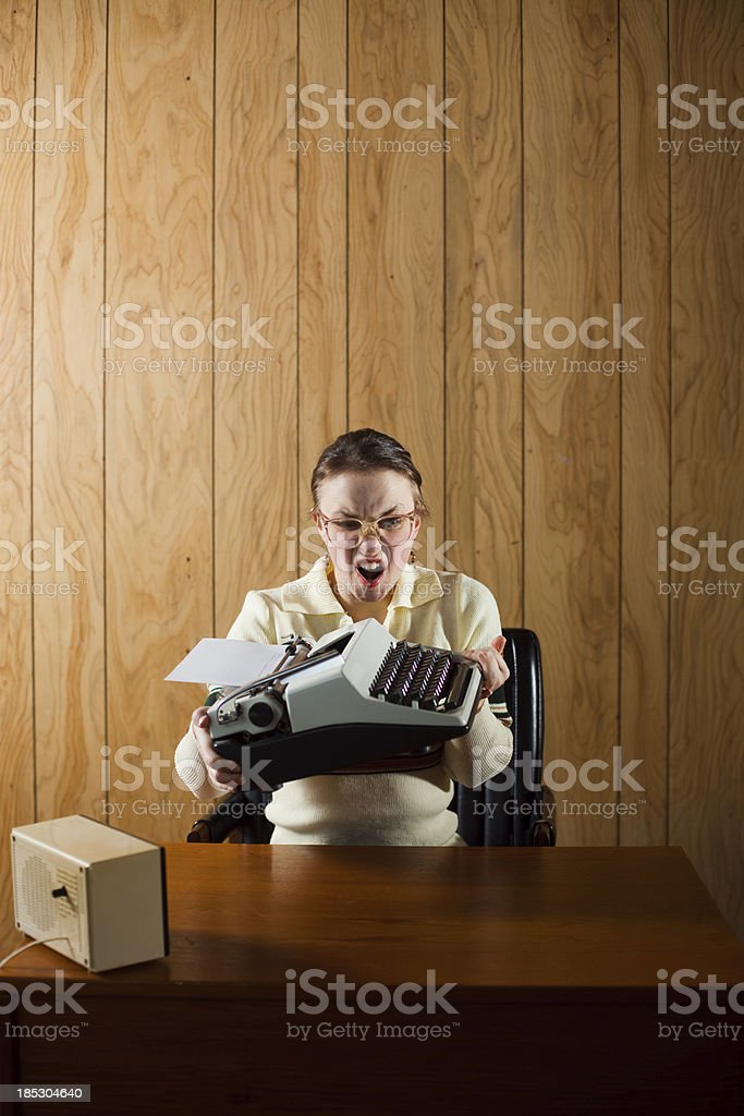 Angry Retro Receptionist Throwing Typewriter royalty-free stock photo