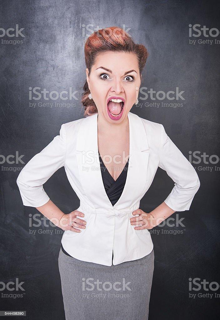 Angry screaming teacher on blackboard background stock photo