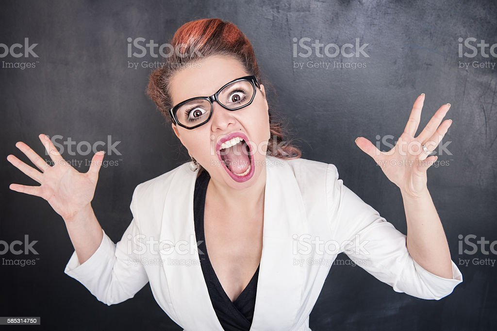 Angry screaming woman on the chalkboard background stock photo