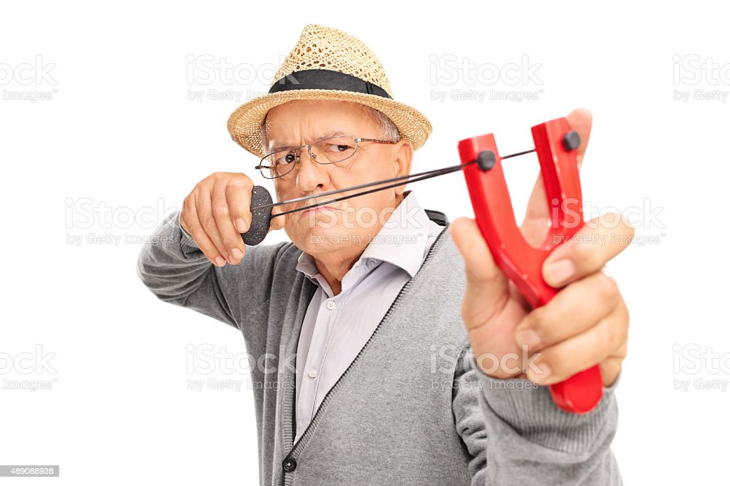 Angry senior aiming to shoot a rock with a slingshot stock photo