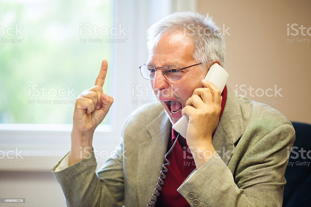 Angry senior businessman yelling at the phone stock photo