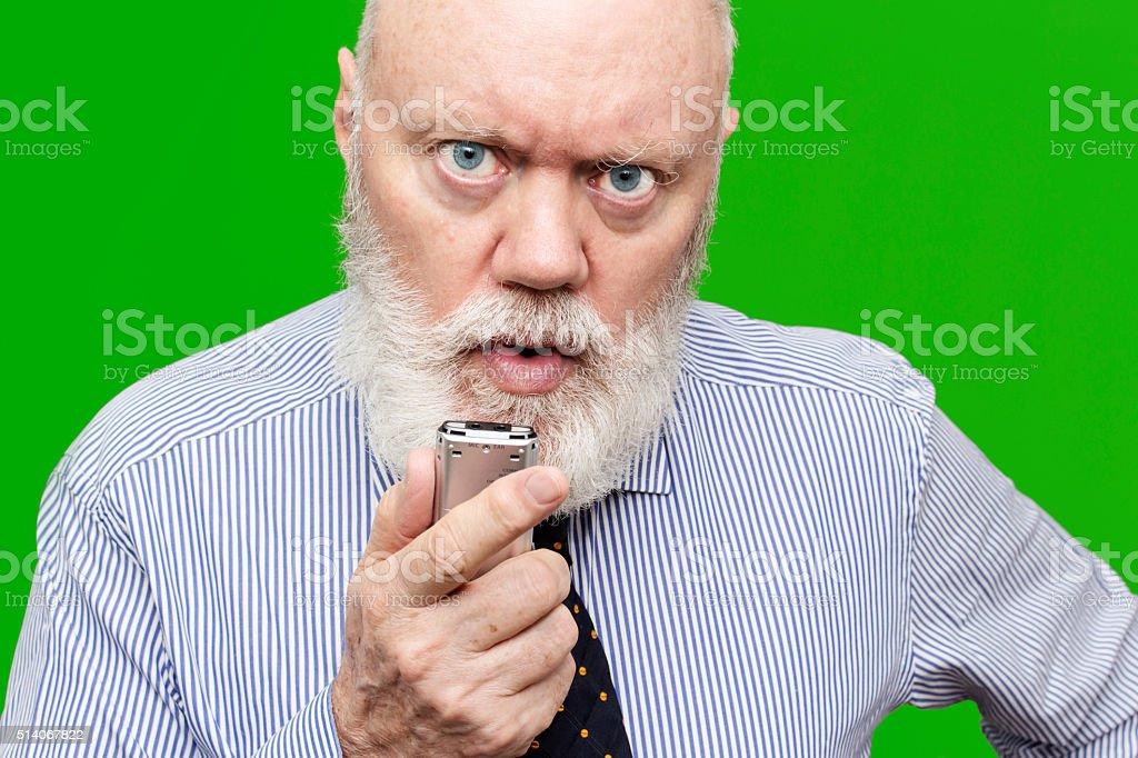 Angry senior speaking to voice recorder stock photo