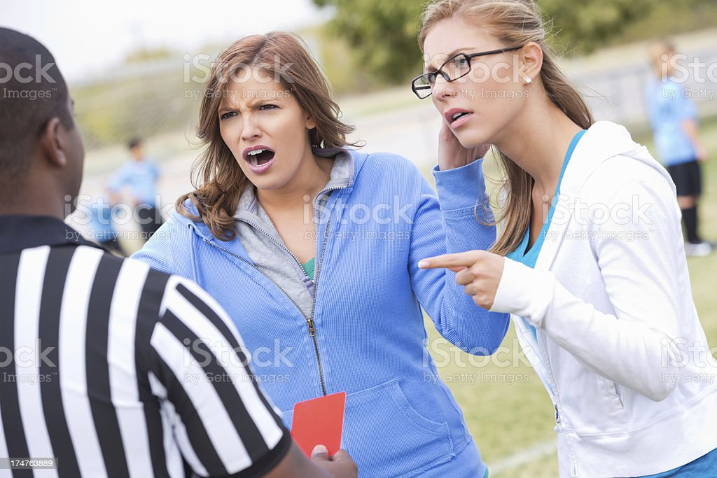 Angry soccer moms yelling at referee during kids' game stock photo