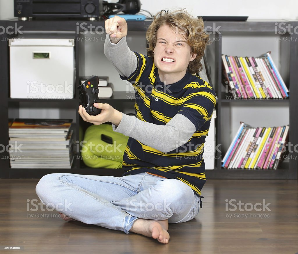 Angry teenage boy  playing  game stock photo