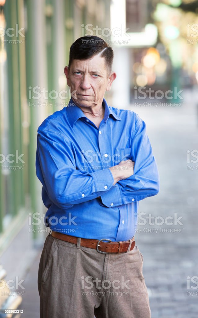 Angry transgender man with folded arms stock photo