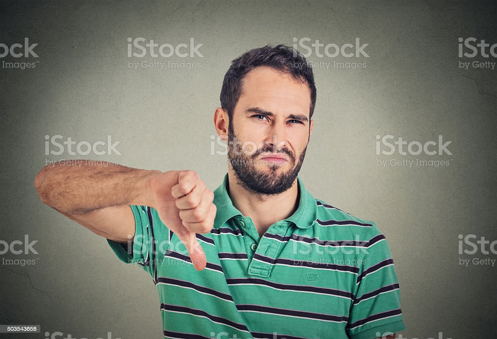 angry, unhappy man showing thumbs down sign stock photo