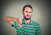 angry, unhappy man showing thumbs down sign