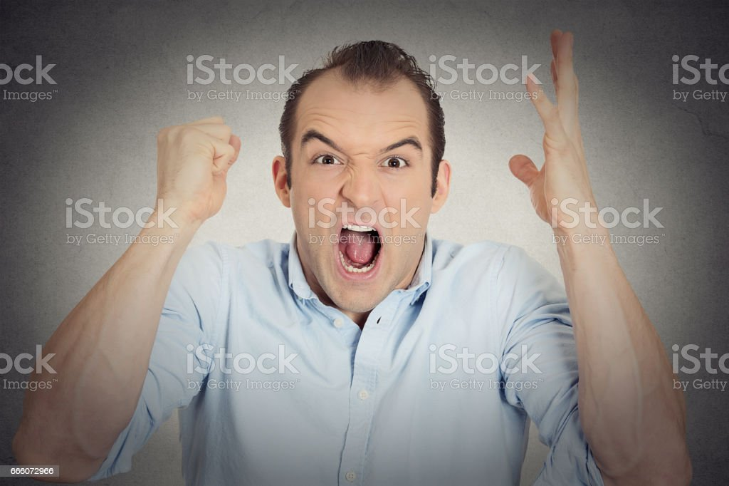 angry upset young man worker mad employee funny looking businessman fist in air open mouth yelling stock photo