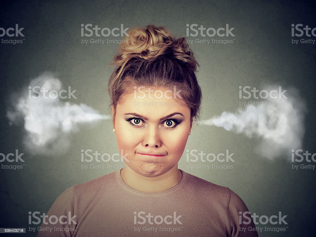 Closeup portrait of angry young woman, blowing steam coming out of...