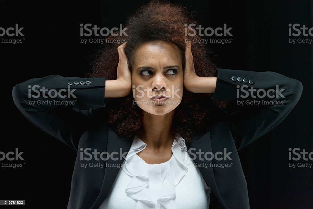 Angry woman covering her ear stock photo