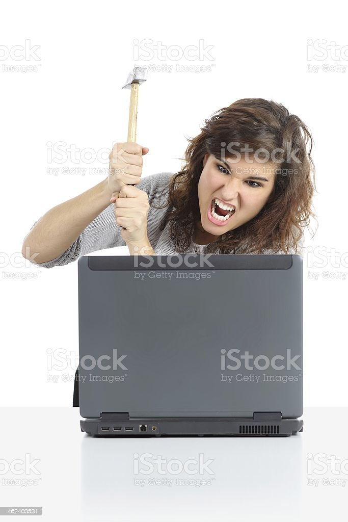 Angry woman destroying a computer with hammer royalty-free stock photo