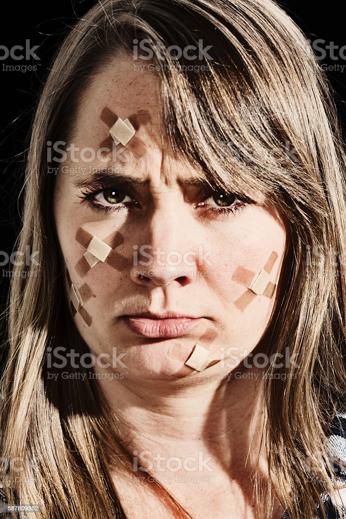 Angry woman, face covered in sticking plasters, frowns stock photo