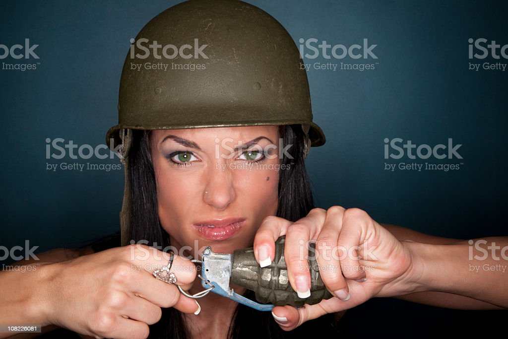 Angry woman holding a grenade and wearing an army helmet stock photo