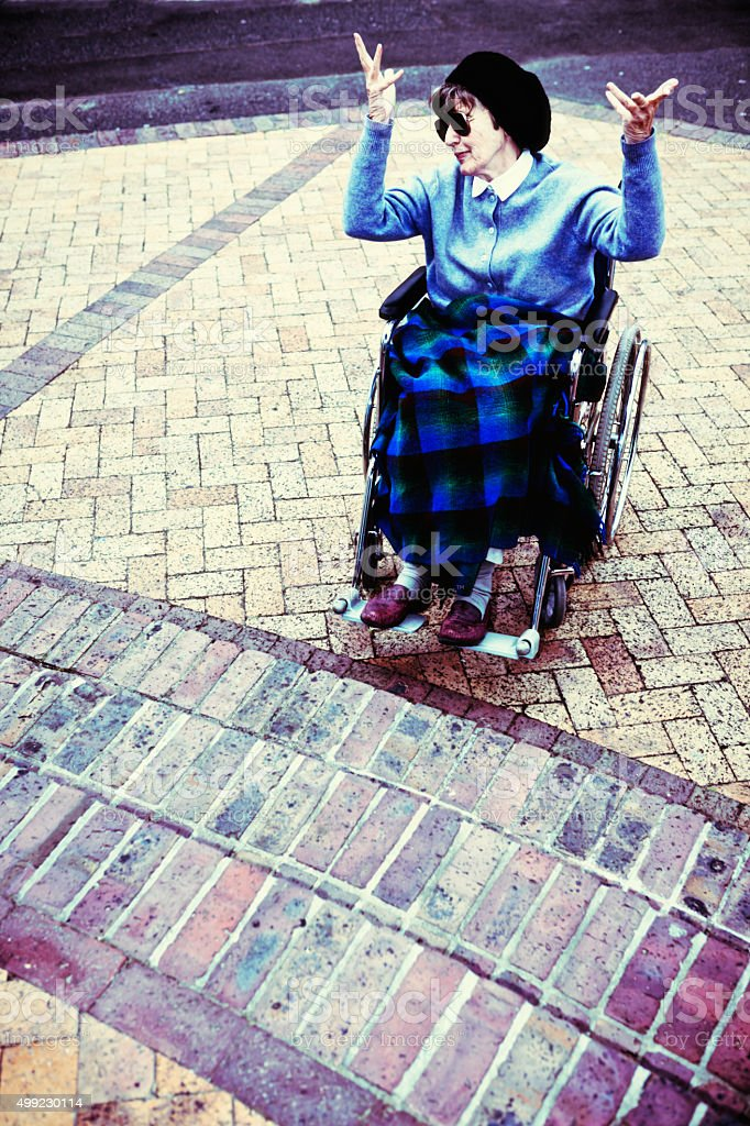 Angry woman in wheelchair is frustrated by flight of steps stock photo