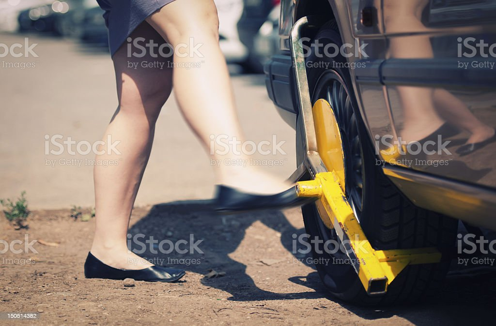 Angry woman kicks wheel lock stock photo